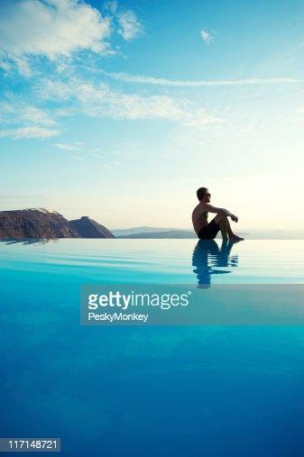 Man Sits Reflecting on Edge of Infinity Pool : Stock Photo