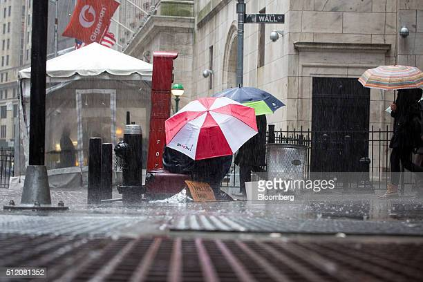 A man sits under an umbrella in the rain on Wall Street outside the New York Stock Exchange in New York US on Wednesday Feb 24 2016 US stocks rose...