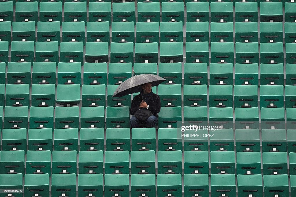 A man sits under an umbrella in the stands as rains falls over the Roland Garros stadium during the Roland Garros 2016 French Tennis Open in Paris on May 31, 2016. / AFP / PHILIPPE