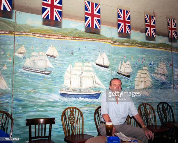 A man sits with a full pint of Guinness in front of a nauticalthemed painted wall in a bar on the Esplanade in the seaside town of Weymouth Dorset...