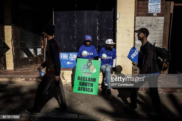 A man sits with a placard calling for South African President Jacob Zuma to be voted out as thousands of opposition parties members march to support...