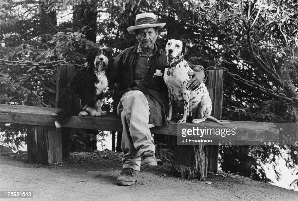 A man sits with his arm around his two dogs California 1968