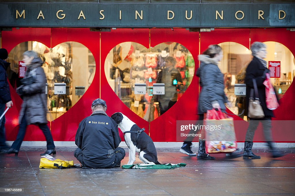 A man sits with his dog and asks for charity outside a Magazin du Nord store in Copenhagen, Denmark, on Monday, Nov. 19, 2012. Denmark's two-year yields sank to the lowest in almost three months in Copenhagen trading as Europe's debt crisis continues to drive investors north. Photographer: Linus Hook/Bloomberg via Getty Images