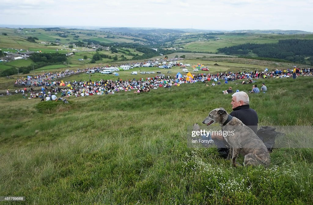 A man sits with his dog and watches the crowds gather as they get ready to watch Stage 2 of the Tour de France on July 6, 2014 in Holm Moss, United Kingdom. The world's greatest cycle race, the Tour de France started for the first time in its history in Yorkshire this weekend. The event has brought thousands of cycling fans to Yorkshire.