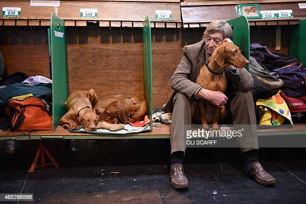 A man sits with his Hungarian Vizsla dog in its stall on the first day of the Crufts dog show at the National Exhibition Centre in Birmingham central...