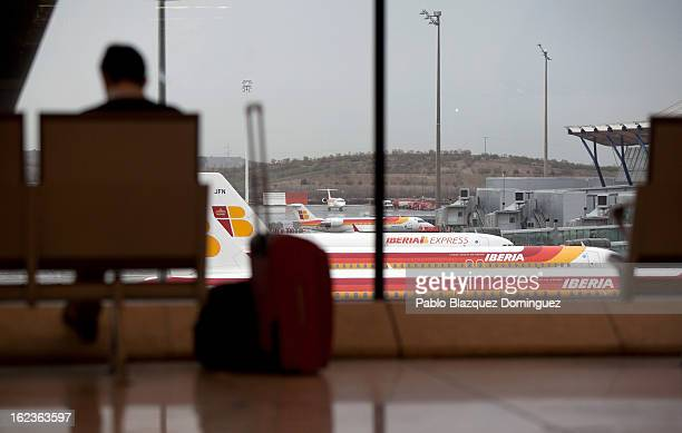 A man sits with his luggage at Barajas Airport while a fleet of Iberia planes are seen parked on February 22 2013 in Madrid Spain Today is the last...