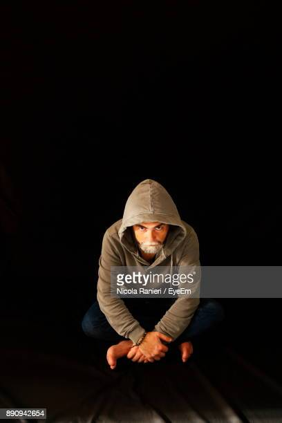 Man Sitting Against Black Background