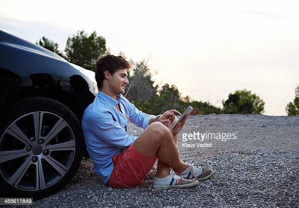 Man sitting against front wheel of car w. tablet