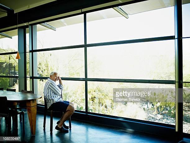 Man sitting alone near window of home