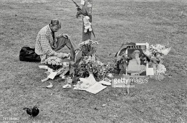 A man sitting alone next to flowers and memorabilia left next to a tree in Kensington Gardens during the public funeral of Diana Princess of Wales in...