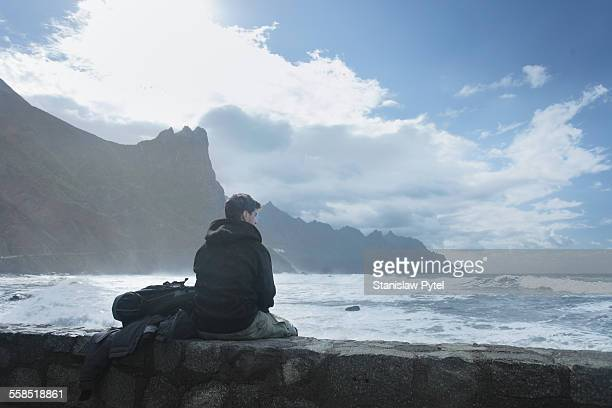 Man sitting and looking at stormy sea, cliffs in b