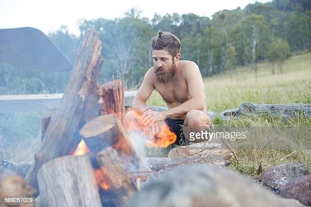 Man sitting around bush fire