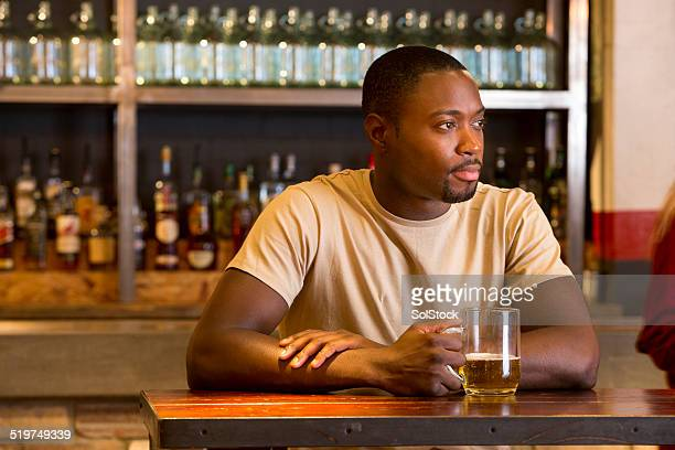 Man Sitting at a Bar with a Beer
