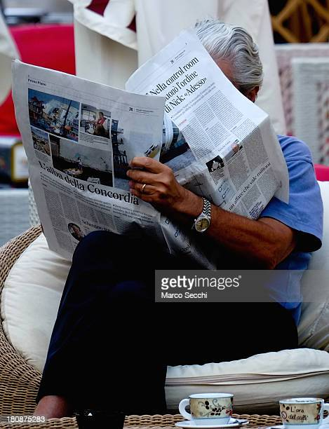 A man sitting at a cafe reads a news paper displaying headlines about the Costa Concordia on September 17 2013 in Isola del Giglio Italy Work began...