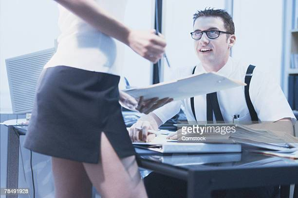 Man sitting at a desk talking with woman