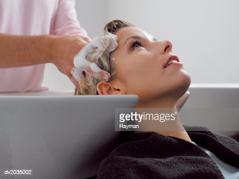 Man Sitting at a Sink Having His Hair Washed by a Hairdresser : Stock Photo