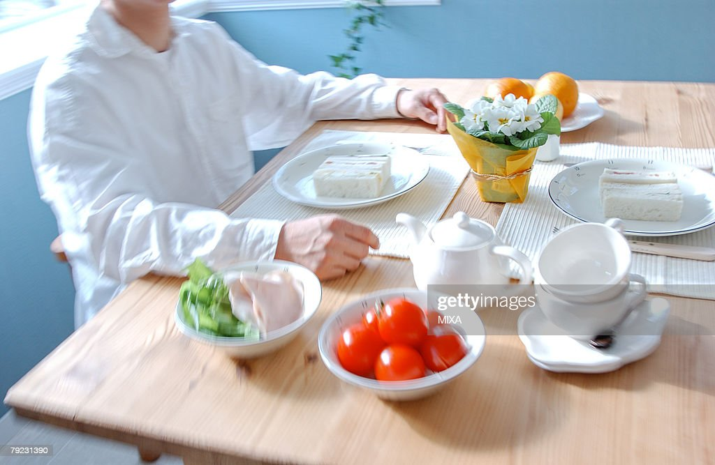 A man sitting at a table for breakfast : Stock Photo
