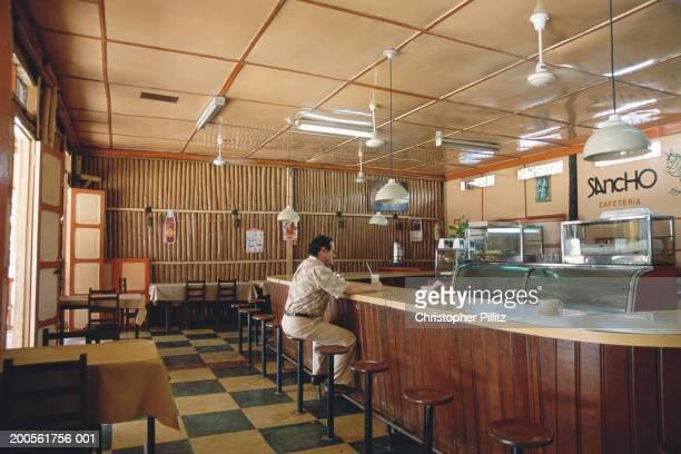 Man sitting at bar counter in restaurant