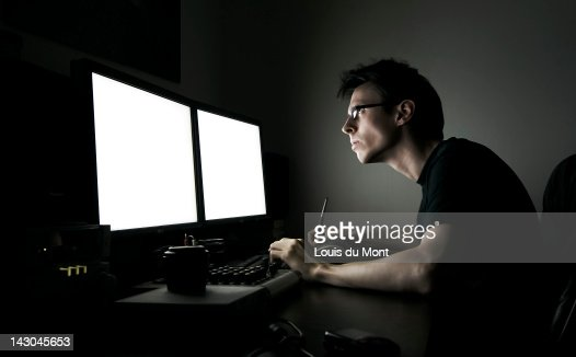Man sitting at computer desk at night : Stock Photo