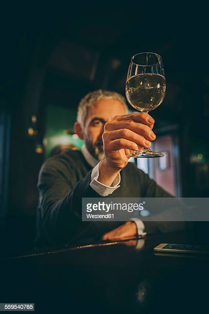 Man sitting at counter of a pub watching white wine glass