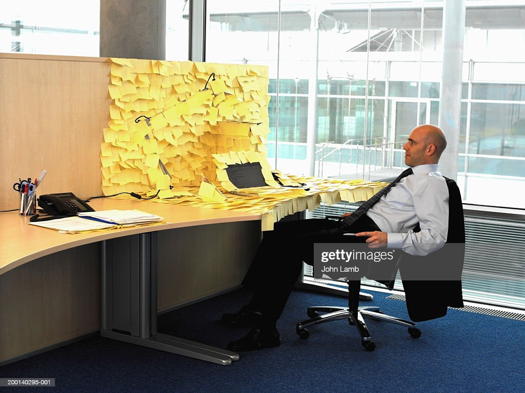 Man sitting at desk covered in yellow memo notes : Stock Photo