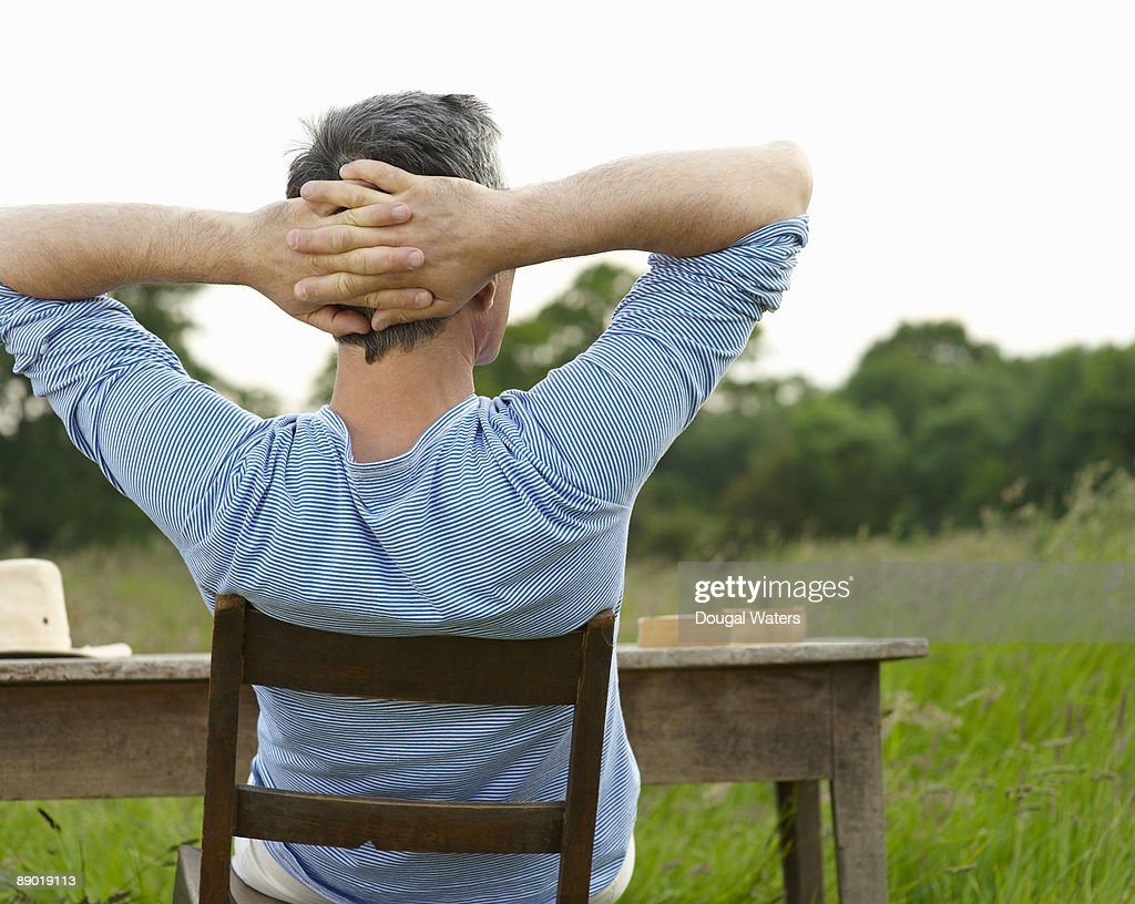Man sitting at desk in countryside meadow.