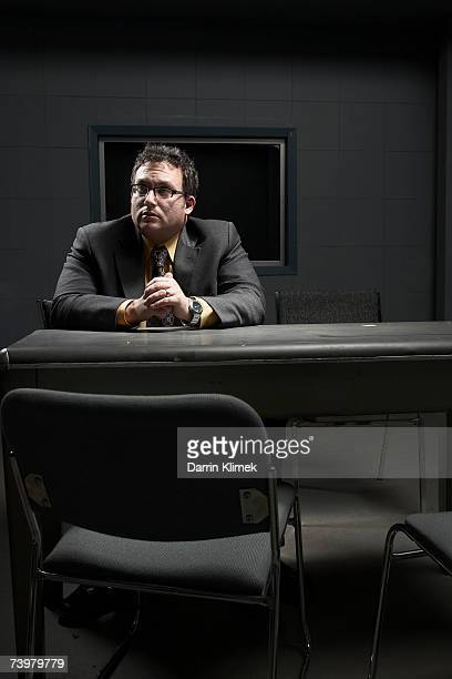 Man sitting at desk in interrogation room, looking away