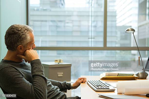 Man sitting at desk in office, looking away in thought