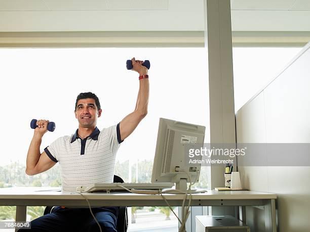 Man sitting at desk lifting weights, smiling