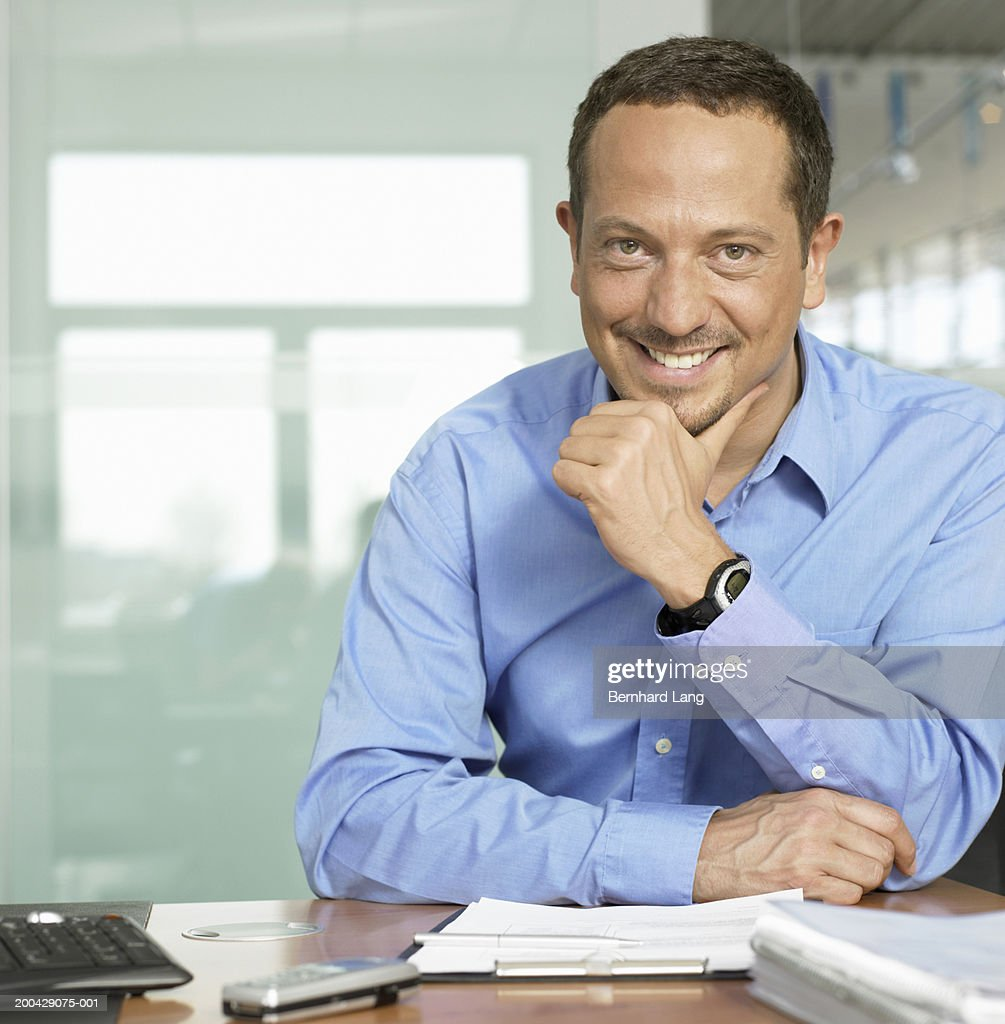 Man sitting at desk resting hand on chin, smiling, portrait : Stock Photo