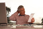 Man sitting at desk scratching head