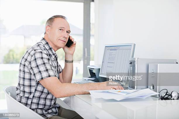 Man sitting at desk using cell phone