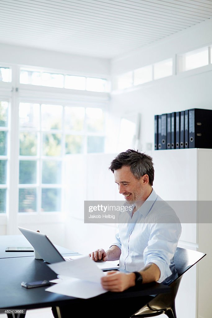 Man sitting at desk with laptop computer and paperwork : Stock Photo