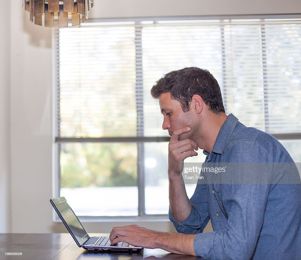 man sitting at desk with laptop computer : Stock Photo