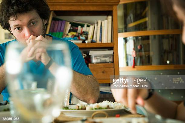 Man sitting at dinner table with hands clasped in front of his mouth