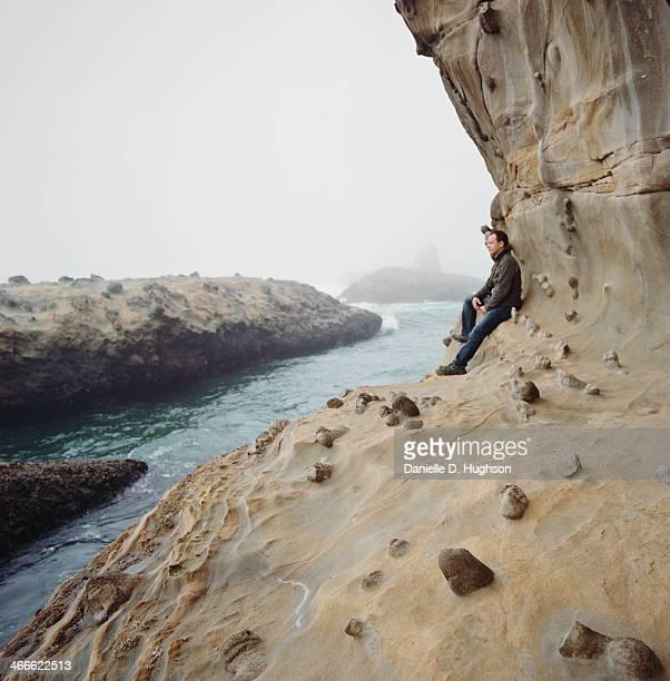 Man Sitting At Edge of Oceanside Cliffs