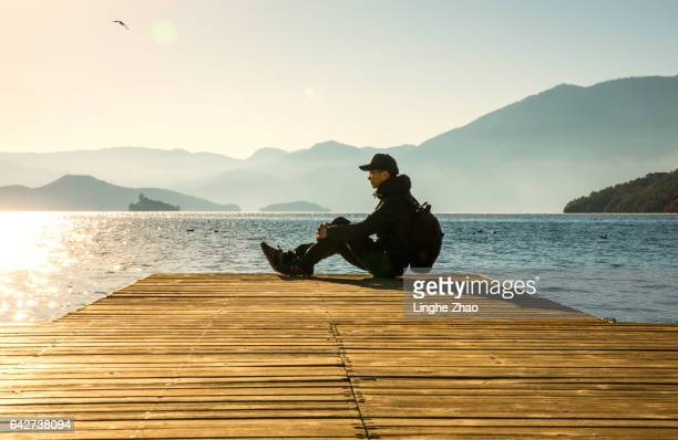 Man sitting at edge of pier