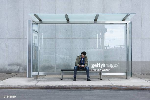 man sitting at glass bus stop with handheld device