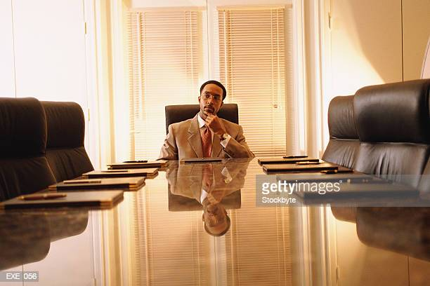 Man sitting at head of boardroom table