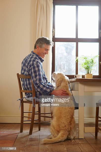 Man sitting at home with pet dog.