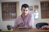 Man sitting at kitchen counter with cup of coffee and digital tablet