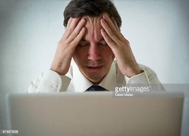 Man sitting at laptop, looking stressed