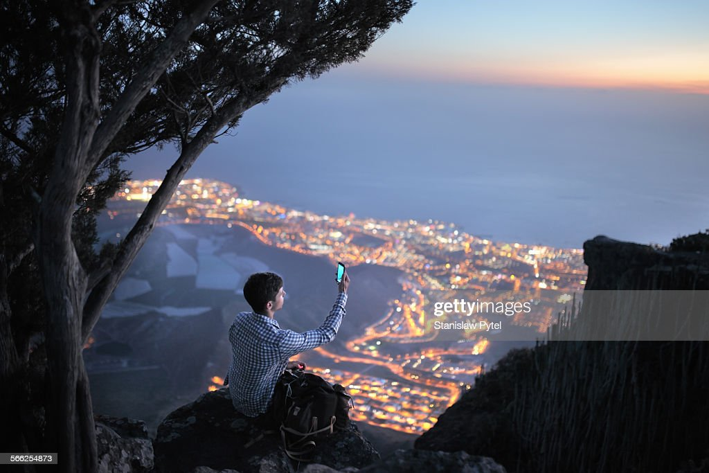 Man sitting at night with mobile device above city