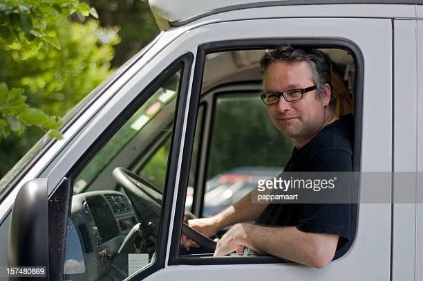 Man sitting at open window and steering wheel van
