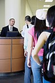 Man sitting at reception desk with line of people