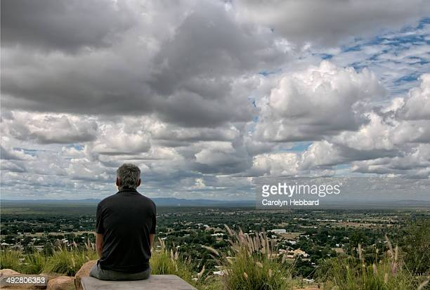 Man Sitting At Scenic Lookout Taking in View