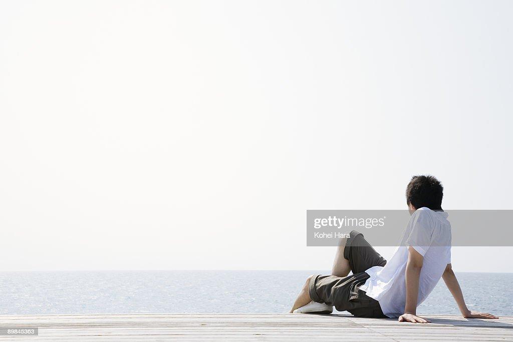 man sitting at seaside : Stock Photo