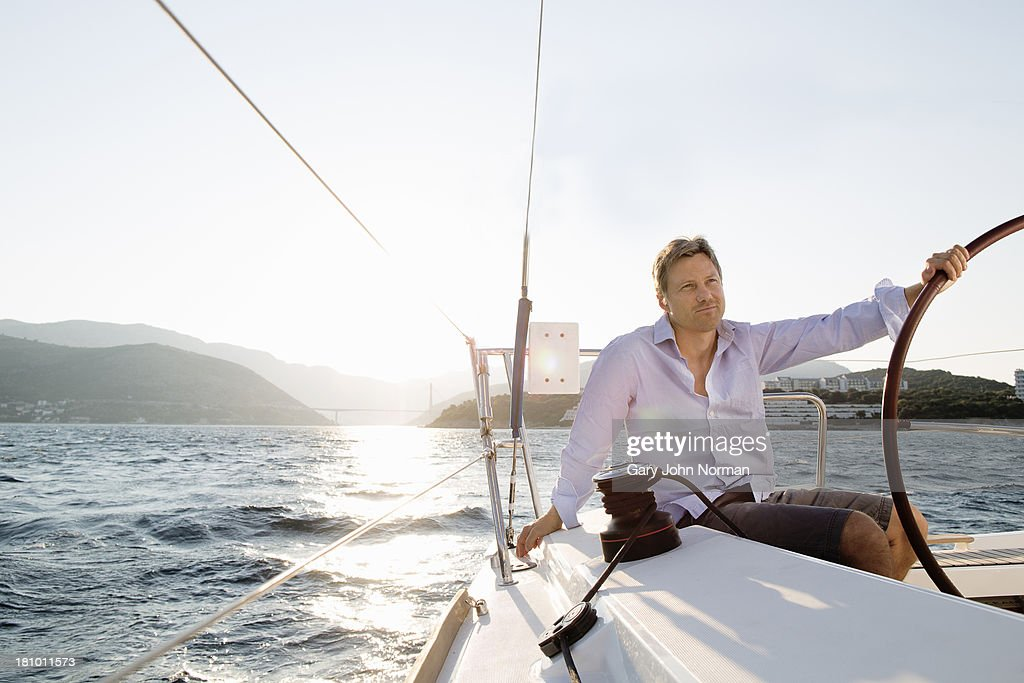 man sitting at stern holding wheel in one hand