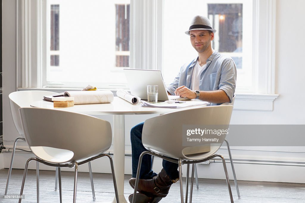 Man sitting at table in restaurant and using laptop : Stock Photo