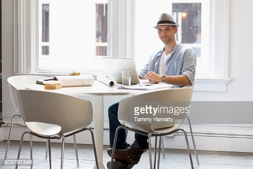 Man sitting at table in restaurant and using laptop : Stock-Foto